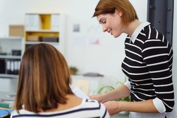zwei kolleginnen besprechen sich am schreibtisch