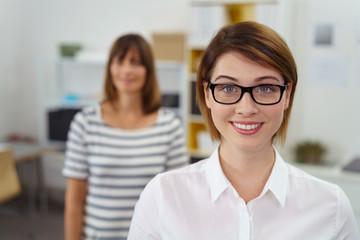 lächelnde mitarbeiterin im büro mit einer kollegin