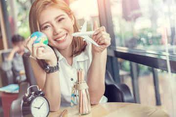 teenage girl hold globe and plane toy in coffeeshop