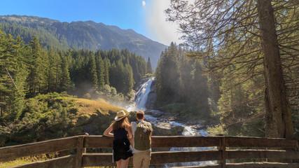 Junges Paar betrachtet die Krimmler Wasserfälle, die höchsten Wasserfälle Europas
