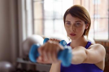 frau trainiert konzentriert im fitnessstudio