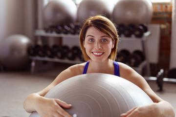 frau trainiert mit einem gymnastikball im studio