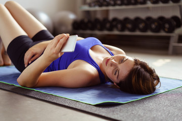 frau im fitnessstudio schaut auf ihr handy