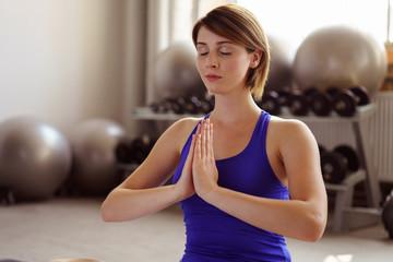 frau praktiziert yoga im fitnessstudio