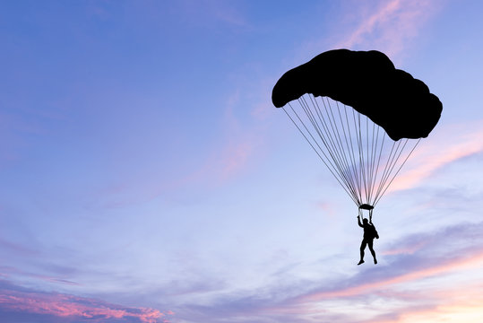 Silhouette of parachute on sunset background