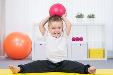 kleiner junge macht gymnastik mit dem ball