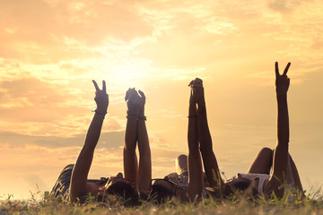 young women lying in the meadow raise their arms in a sign of friendship