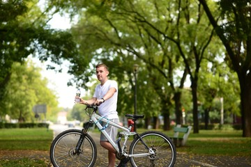 Young blond man on bicycle stoping to drink water