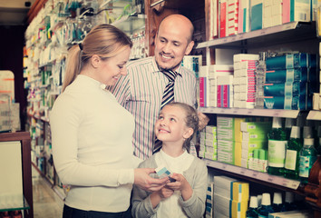 Mother and father with kid picking in pharmaceutical store