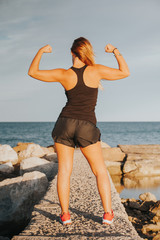 Young girl showing strong biceps after outdoors fitness workout. Fitness woman. Whole body back view.