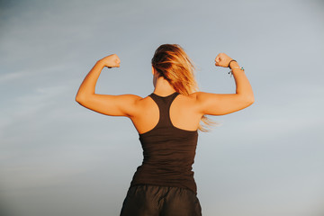 Young girl showing strong biceps after outdoors fitness workout. Fitness woman. Back view.