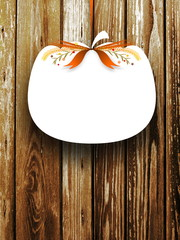 Close-up of one blank pumpkin shaped frame hanged by brown ribbon on brown wooden boards background