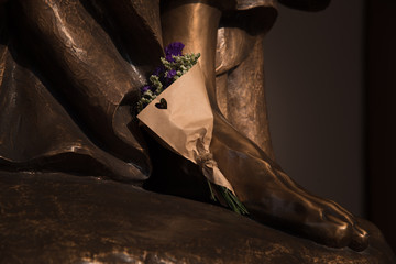 A bouquet wrap by brown paper putting on the foot of copper's statue