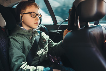 Boy watch a tablet on the car back seat
