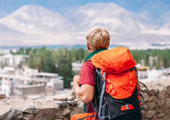 Backpacker tourist looks on blue mountain