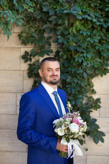 The groom in a stylish blue suit