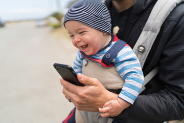 7 month old baby boy playing with dad's phone