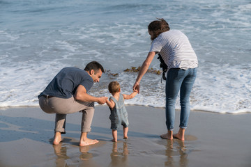 10 month old baby boy walks with mom and dad on the beach