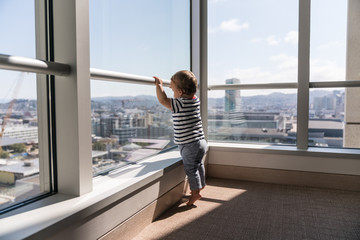 10 month old baby boy tip toes to see out of window in high rise