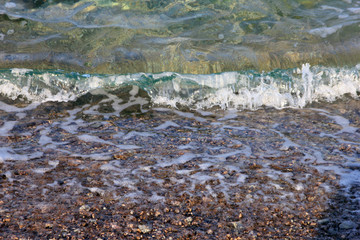 sea surf with turquoise wave on crimean pebble beach in summer s