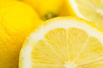 Wall Mural - Saftige Zitronen im Licht der Sommersonne. Reife Zitronen. Zitronen in Scheiben und ganz.