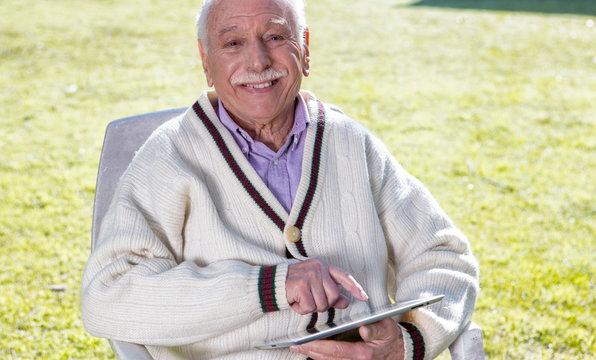Elder senior happy in the garden using tablet