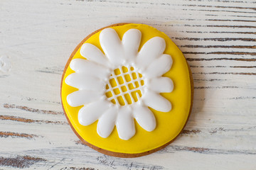 Round cookie with flower picture. Yellow and white frosting. Flavor and beauty. Delicious glazed biscuit.