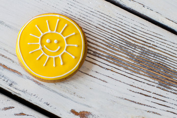 Cookie with smiling sun picture. Yellow frosted biscuit. Simplest recipe of joy. Sweet pastry made at home.