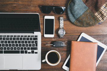 Flat lay design of men´s office objects, including laptop, coffee, car keys, book.