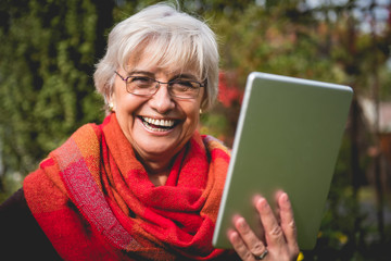 Beautiful mature woman smiling and using new technologies