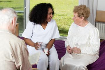 Nurse in rehab facility speaking to elder patients