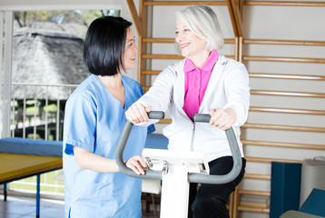 Elder retired woman assisted by nurse in rehab facility