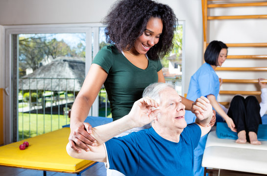 Elder retired man assisted by nurse in rehab clinic