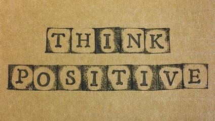 Words Think Positive make by black alphabet stamps on cardboard.