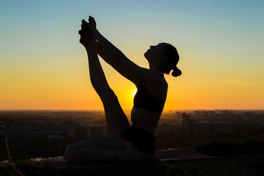 Silhouette of sporty woman doing yoga in floating boat pose in the park at sunset. Sunset light, sun lens flares, golden hour. Freedom, health and yoga concept. Dolly shot