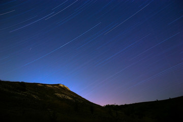 Star trail in the night sky. The slope of the mountain on a back