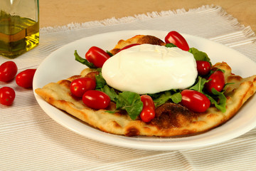 Burrata cheese with tomatoes and arugula on focaccia.
