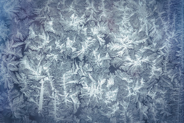 Frost pattern as Christmas background on frozen window during Christmas holidays