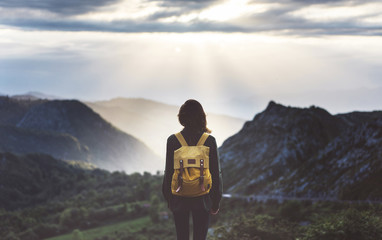Wall Mural - Hipster young girl with bright backpack enjoying sunset on peak of foggy mountain. Tourist traveler on background valley landscape view mockup. Hiker looking sunlight flare in trip Picos de Europa