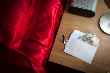 Prostitution concept with money in an envelope on a nightstand in a hotel room, representing the payment for a prostitute, escort or sex worker, next to the bed covered in red satin sheets