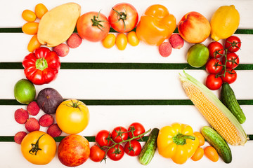 Juicy fruits and vegetables in a circle at the white boards background. Free space for text in the center. Top view.
