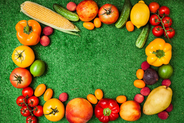 group of fruits and vegetables arranged in a circle on a background of green grass. Free space for text in the middle.Group of fruits and vegetables