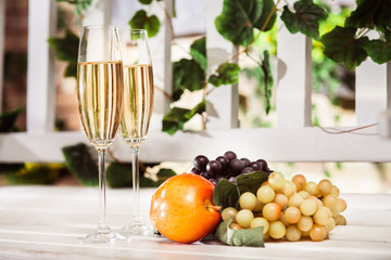 Autumn fruits and two glasses of white wine at the light background. Horizontal