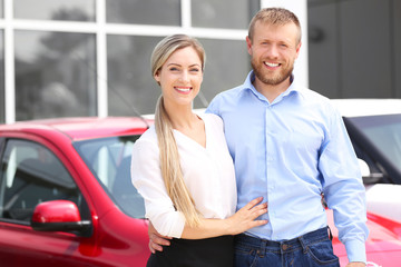 Young couple on new cars background