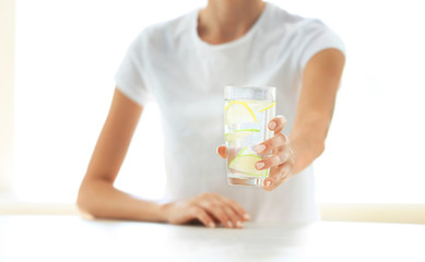 Girl holding fresh drink at table on kitchen