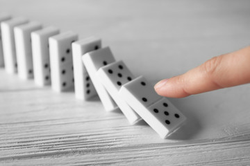 Female hand pushing dominoes on wooden table