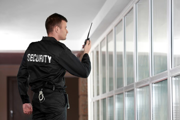 Security man with portable radio in corridor