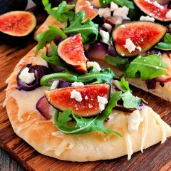 Autumn flat bread pizza with figs, arugula, and goat cheese, close up ...