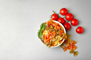 Plate with farfalle pasta and tomatoes on table