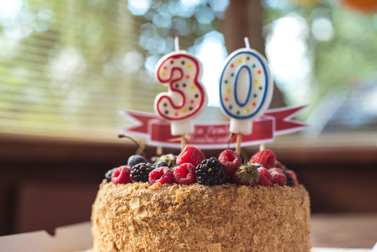raspberries blackberry birthday cake with candles number 30
